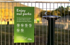 fence-mounted-park-regulatory-sign-near-water-fountain
